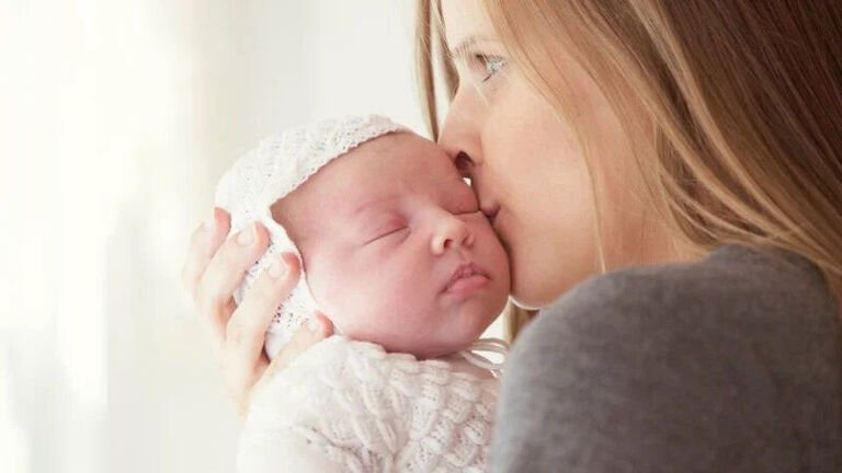 A mother kisses the forehead of her newborn baby.