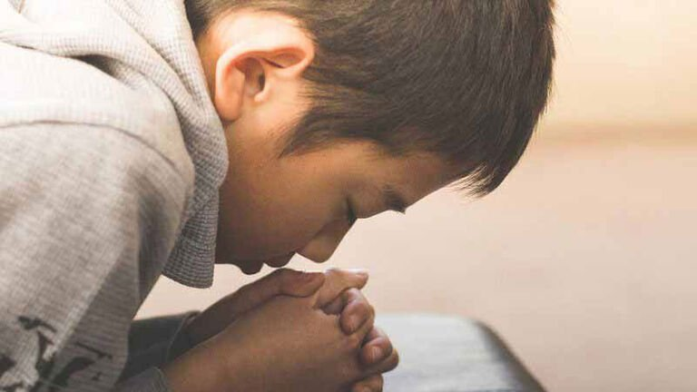 A young boy prays over a book. His BLESSED First Communion sacramental preparation taught him the value of prayer.
