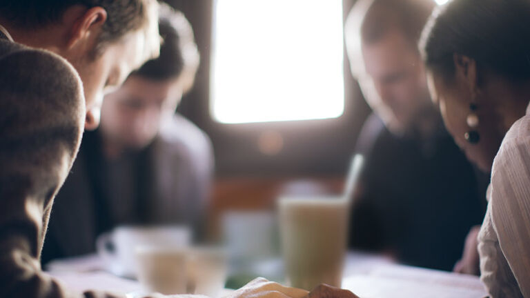 A group of three men and a young woman sit together hand in hand at a coffee shop with their heads down and eyes closed in prayer with their praying journals in front of them