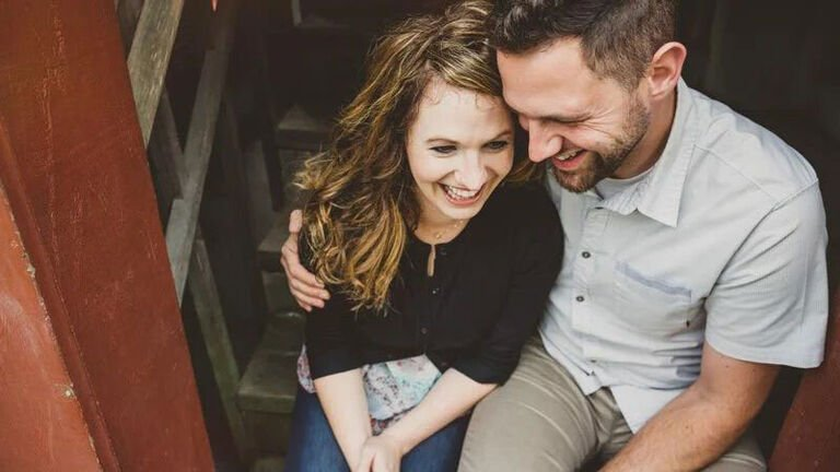 A newly engaged couple sits on the stairs excited to start their life together.