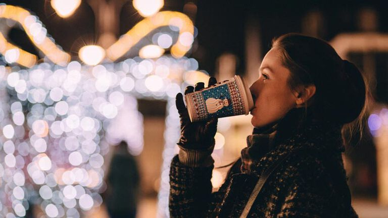 A young woman stands outside bundled up with a scarf and gloves drinking hot chocolate while looking at bright christmas lights during the advent season