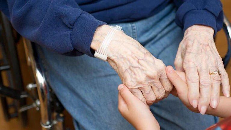 A young child holds the hands of his grandmother.