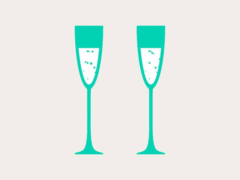 Two tall emerald green champagne glasses stand next to each other filled with a white and bubbly drink
