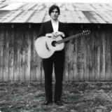 black and white profile of eliot morris standing in front of a barn with a guitar over his shoulder and his hands resting on top